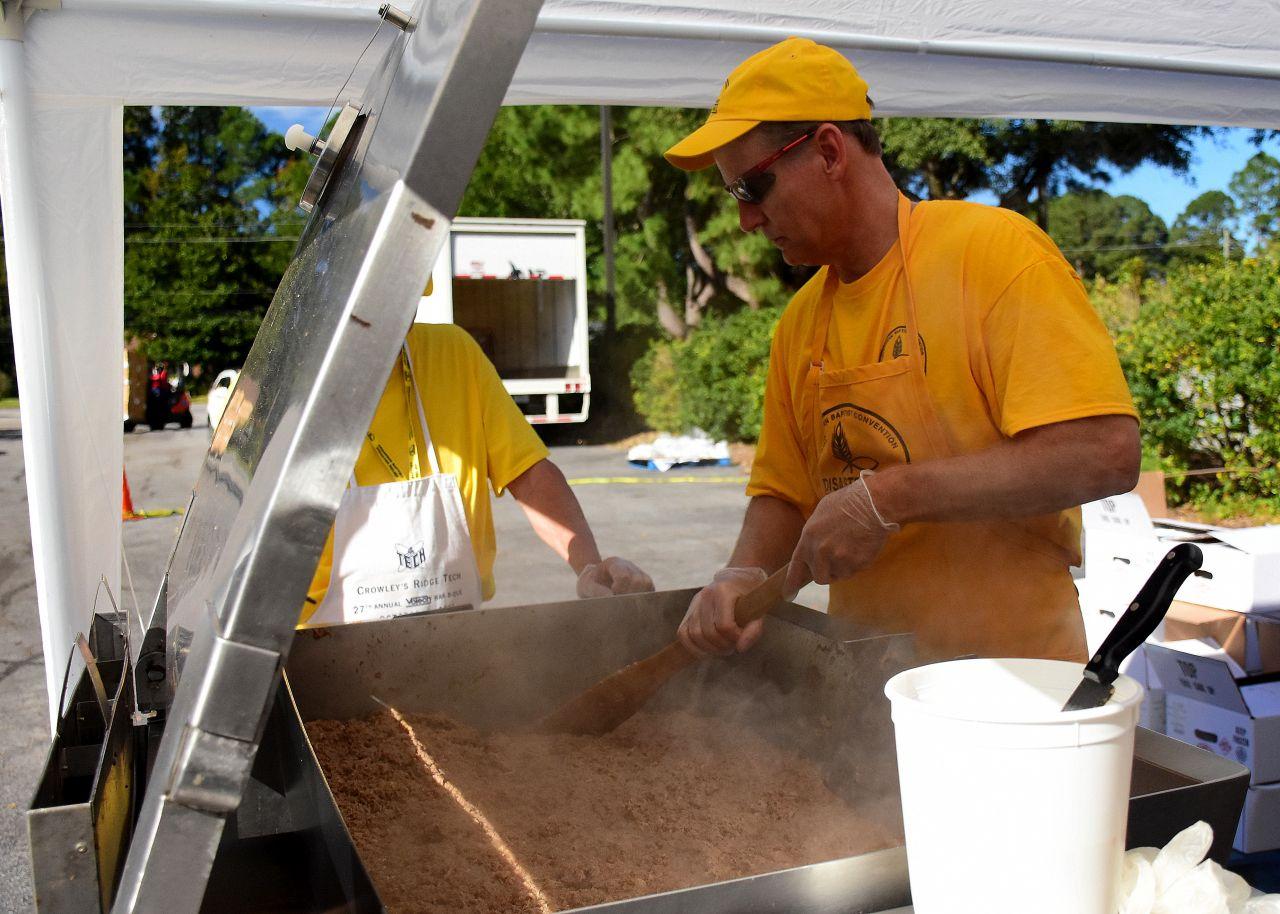 Dennis McGee stirring pulled pork in a 42 gallon tilt-skillet
