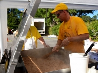 Dennis McGee stirring pulled pork in a 42 gallon tilt-skillet