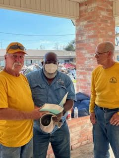 DR team members offer a Bible to a Houma resident they served.