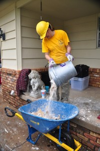 A Baptist mud-out volunteer pours a bucketful of debris into a wheel barrel to be hauled off. (Photo: David Crowell)