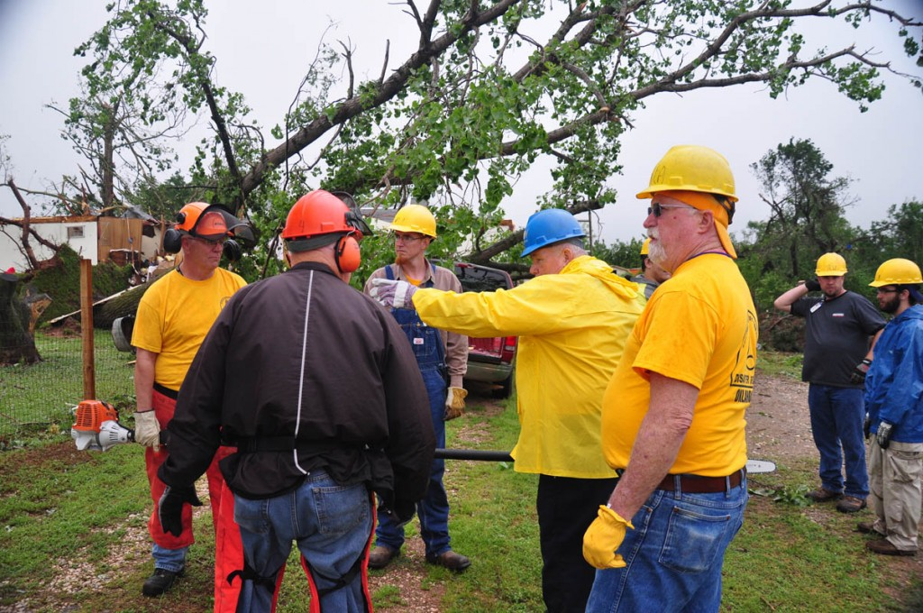 Debris removal team leader Deyrl Kastner (In blue hard hat) outlines plans for removing debris from a property in the Bridge Creek area. (Photo: David Crowell)