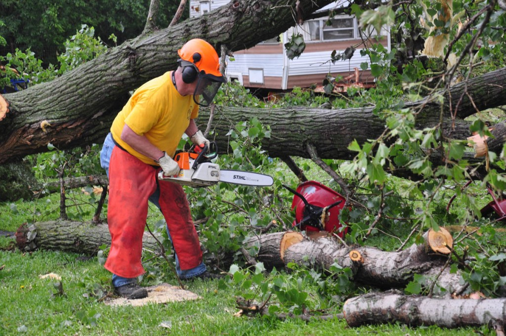 Dennis Troyer with Oklahoma Baptist disaster relief unit works on cutting up a fallen tree in the Bridge Creek area. (Photo: David Crowell)