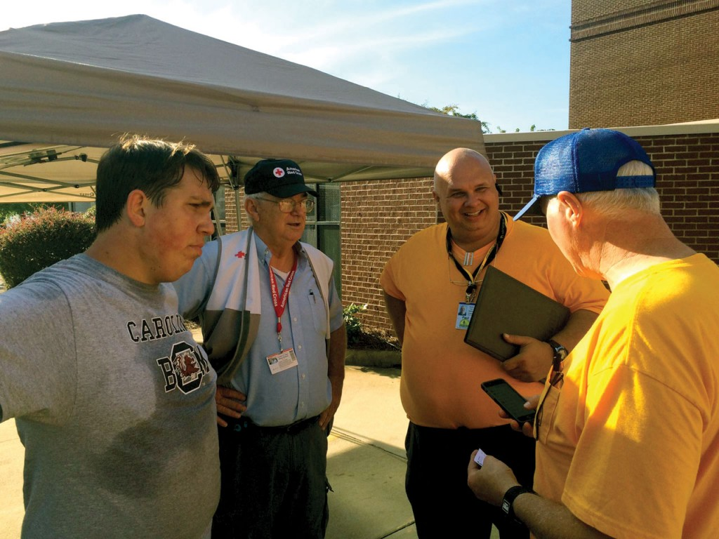 Steve Wise and Paul McKee, right, both South Carolina Blue Caps, discuss feeding plans with American Red Cross Kitchen Manager Bobby Roberts, second from left, and a local volunteer. The kitchen was set up at Riverland Church in Irmo, S.C. (photo: SBDR)