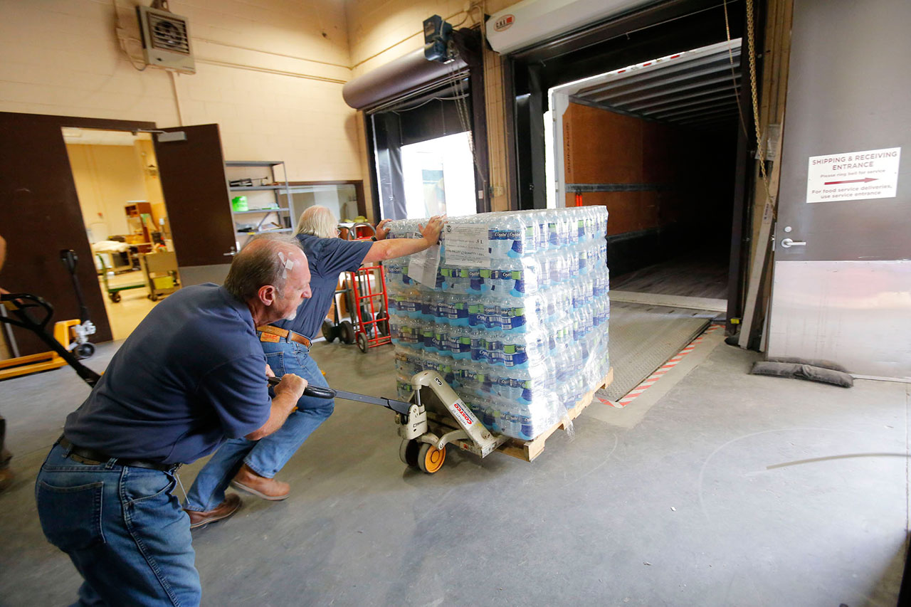 Southern Baptist Disaster Relief volunteers Dale Price (left) and Serge Renard, load a pallet of water headed for South Carolina to aid survivors of historic flooding in the state and neighboring North Carolina. Photo by Susan Whitley