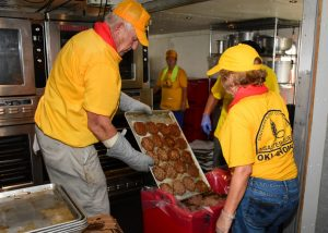 Oklahoma Disaster Relief volunteers Bob Goekler and Kendal Miller fill a container with hamburger patties to be delivered to flood victims. (Photo: David Crowell)